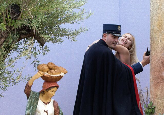 A gendarme from the Vatican's security forces stops a Ukrainian feminist group Femen activist after she snatched the statue of Baby Jesus from the Nativity scene set in St. Peter's Square at the Vatican, Thursday, Dec. 25, 2014.