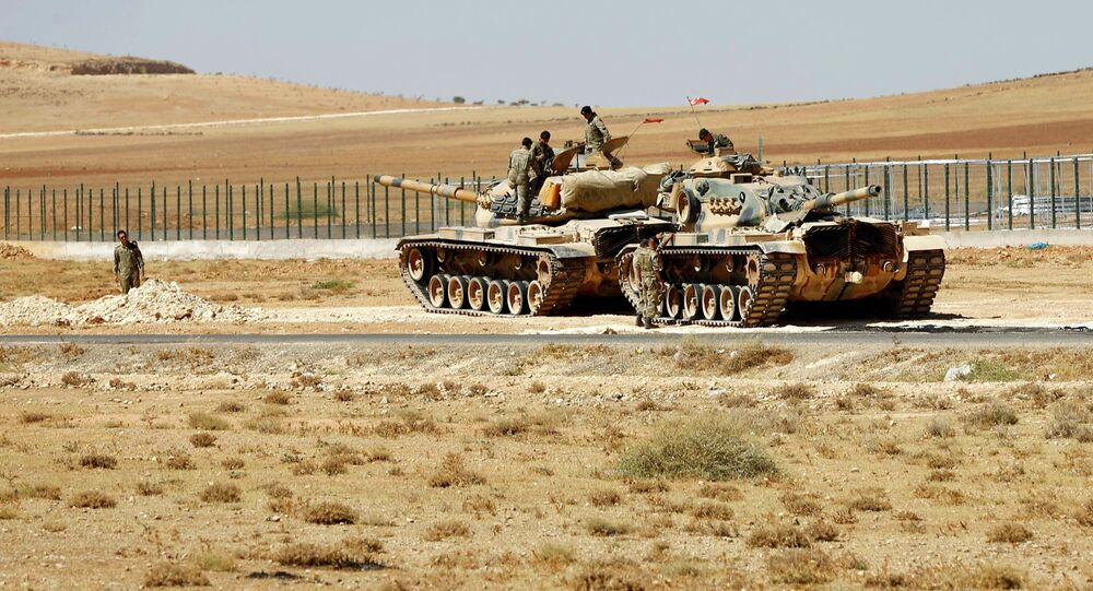 Turkish soldiers stand on top of tanks next to the Syrian-Trukish border fence (file photo)