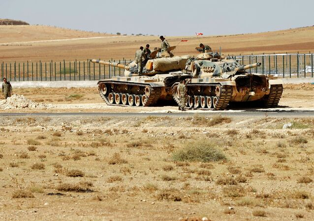 Turkish soldiers stand on top of tanks next to the Syrian-Turkish border fence. File photo