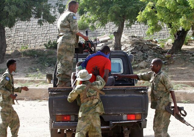 A blind-folded suspect is detained by Somalia security forces