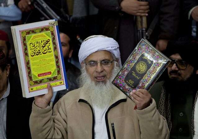 Maulana Abdul Aziz, the Red Mosque cleric and member of the Taliban negotiating team shows religious books to media during a news conference in Islamabad