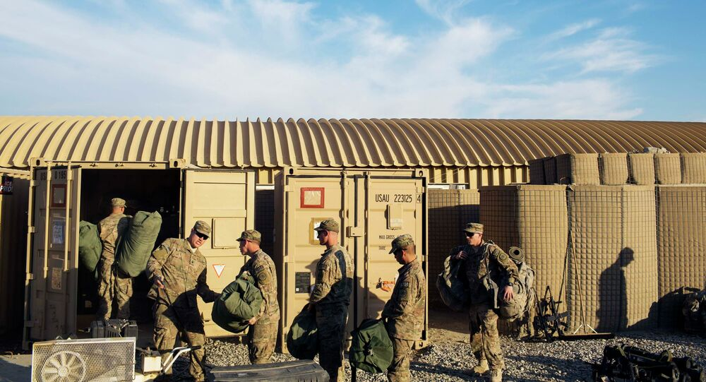U.S. soldiers from D Troop of the 3rd Cavalry Regiment load bags into a container in preparation for leaving Afghanistan