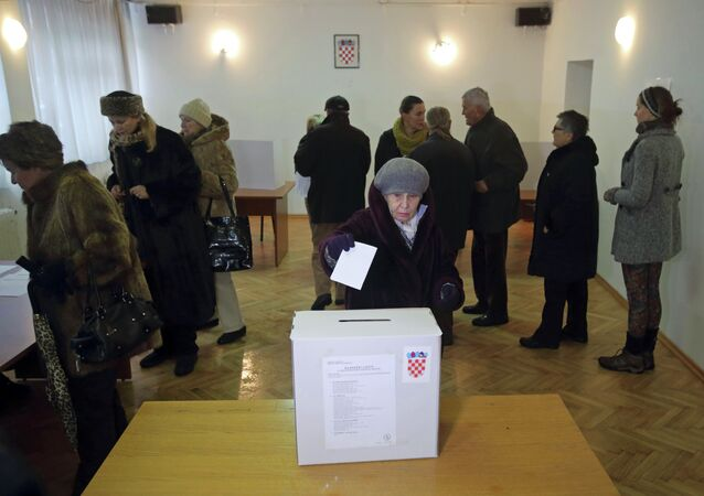 A woman casts her ballot at a polling station during the presidential election in Zagreb