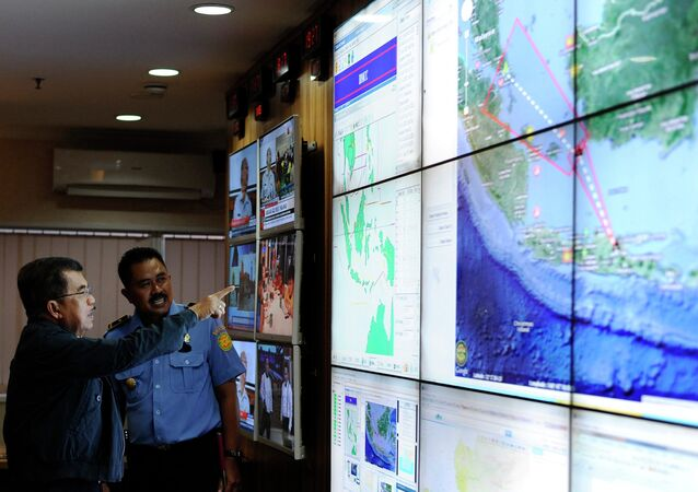 Indonesia's vice-president Jusuf Kalla (L) monitors progress in the search for AirAsia Flight QZ8501 during a visit to the National Search and Rescue Agency