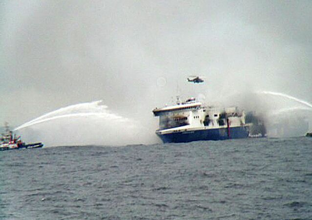 A rescue helicopter flies over the burning car ferry Norman Atlantic as fire fighting tug boats douche the vessel in south Adriatic sea