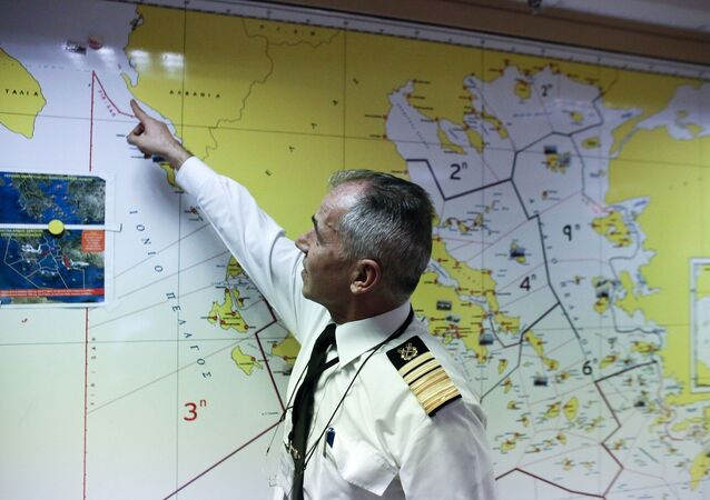 Athanasios Athanasopoulos chief of Greece's coast guard indicates the last known position of the stricken Italian flagged Norman Atlantic ferry, at the Merchant Marine operation room in Piraeus port, near Athens