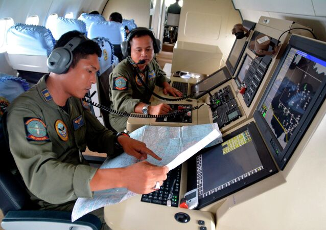Two members of the Indonesian Navy's Tactical Commanding Operator (TACCO) help with the search for AirAsia flight QZ 8501