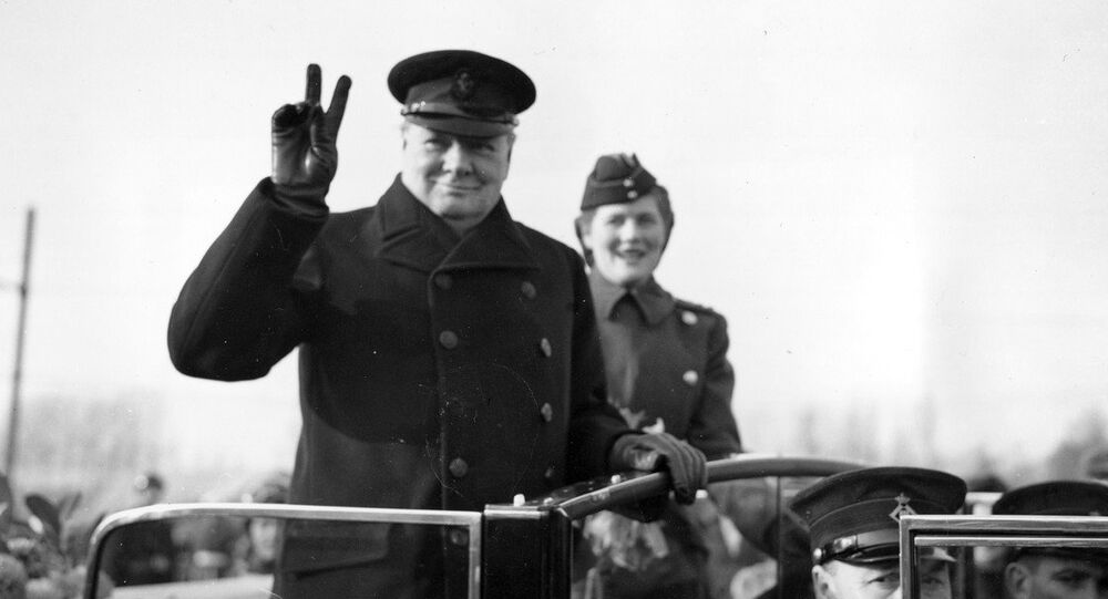 Winston Churchill holds up two fingers to make a V-sign for Victory as he salutes from an open car in Antwerp, Belgium, on Nov. 17, 1945