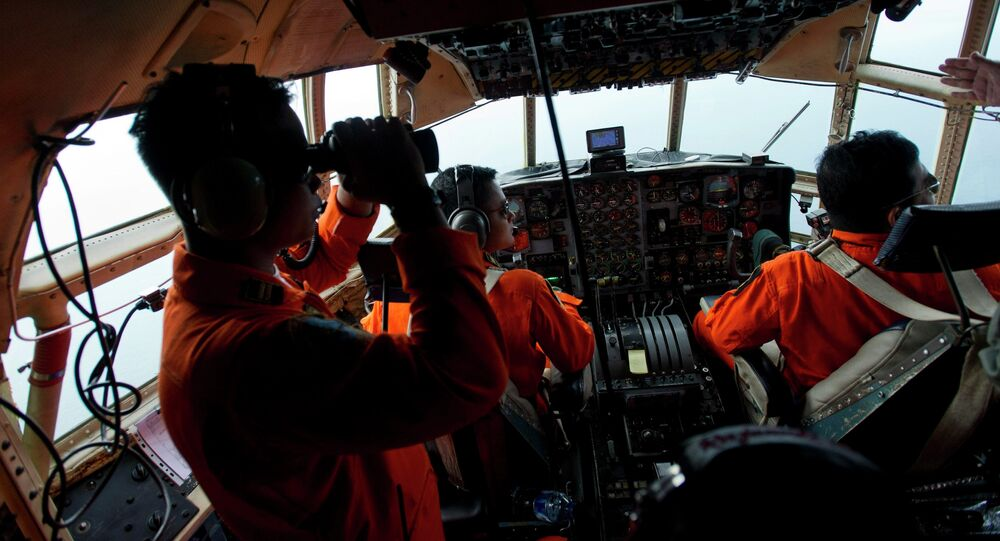 Airforce soldiers onboard a Hercules C130 stand monitor the Belitung Timur sea during search operations for AirAsia flight QZ8501 near Belitung island, December 29, 2014