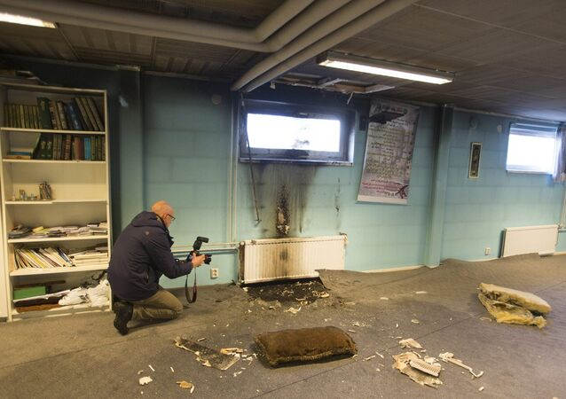 Police officers investigate a suspected arson attack after a fire in the basement of a mosque in the southern Swedish town of Eslov, Monday Dec. 29, 2014