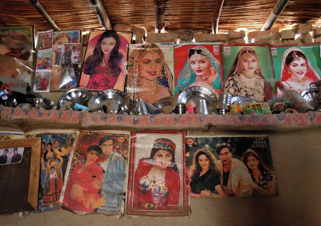 Utensils placed on a mud wall shelf adorned with Bollywood film star posters are seen in a room owned by a cotton picker's family in Meeran Pur village, north of Karachi November 23, 2014