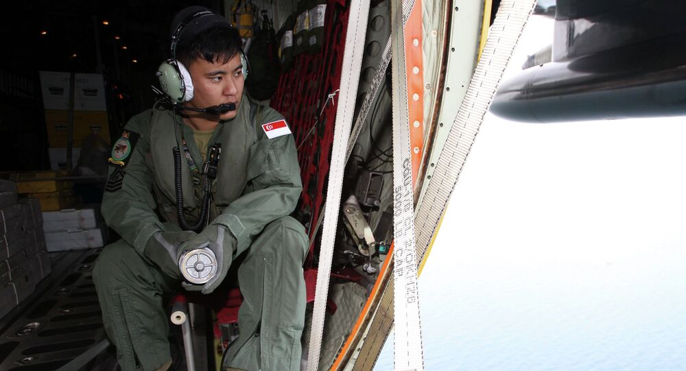 A member of the Republic of Singapore Air Force (RSAF) looks out into the waters, onboard a C-130 Hercules, during a Search and Locate operation for the missing AirAsia QZ8501 aircraft over an undisclosed search area December 29, 2014