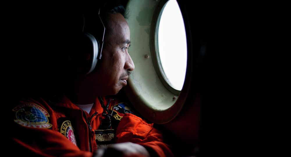 A member of an Indonesian Hercules C130 aircrew watches through a window while monitoring the Belitung Timur sea during search operations for AirAsia flight QZ8501 near Belitung island, December 29, 2014