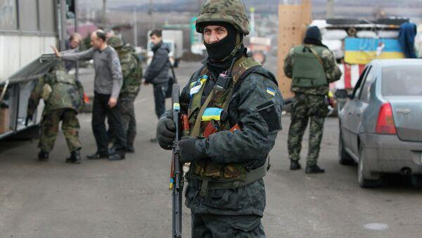 Ukrainian serviceman guards as his comrades check a civilian transport near the eastern Ukrainian town of Debaltseve in Donetsk region, December 24, 2014 - Sputnik International