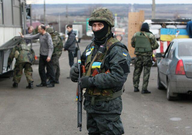 Ukrainian serviceman guards as his comrades check a civilian transport near the eastern Ukrainian town of Debaltseve in Donetsk region, December 24, 2014