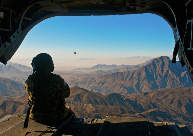 U.S. Army Spc. Devon Boxa, 7-158th Aviation Regiment, admires the Afghanistan landscape out the back door of her CH-47D Chinook helicopter as another Chinook follows