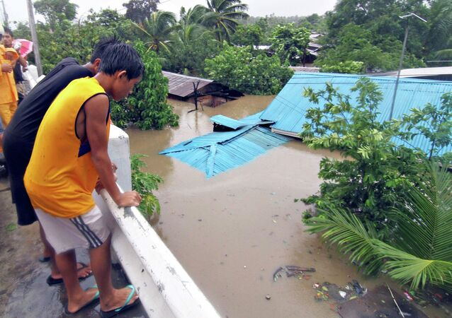 Residents stand on a bridge overlooking their homes submerged in floodwaters during heavy flooding brought by tropical storm Seniang in Misamis Oriental, on Mindanao island in southern Philippines December 29, 2014