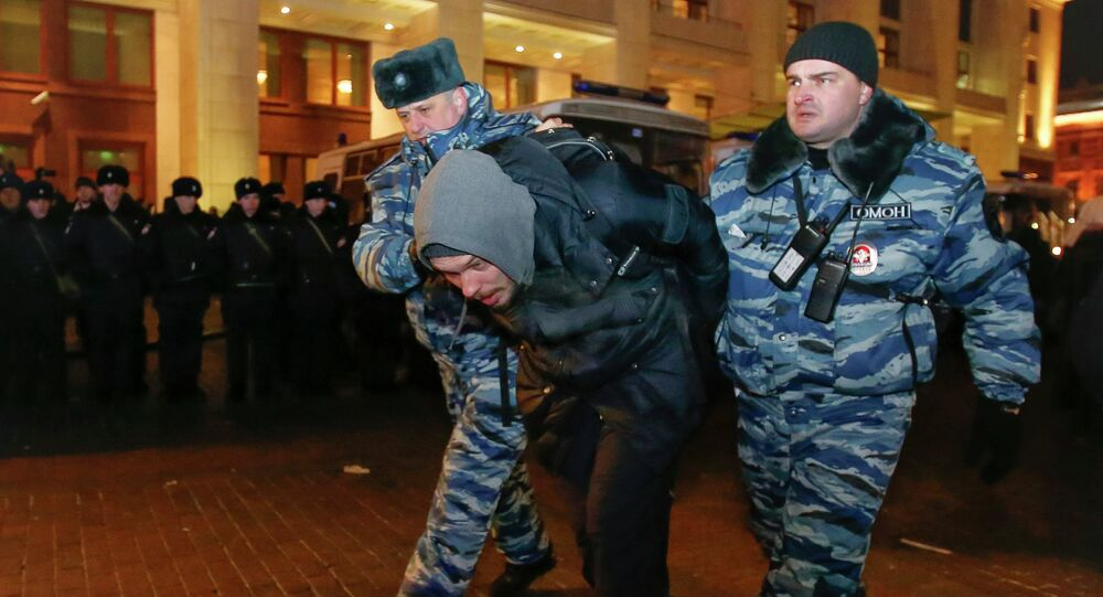 Policemen detain a supporter of Russian opposition leader and anti-corruption blogger Alexei Navalny