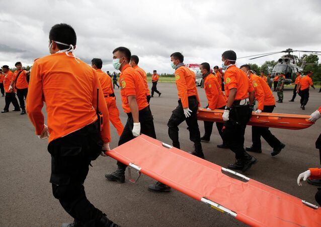 Indonesian Search and Rescue crews walk out to meet a helicopter carrying the bodies of two AirAsia passengers recovered from the sea, at Iskandar airport in Pangkalan Bun, Central Kalimantan, December 31, 2014