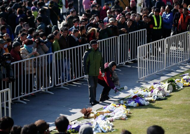 People lay down flowers during a memorial ceremony in memory of people who were killed in a stampede incident during a New Year's celebration on the Bund, in Shanghai January 1, 2015