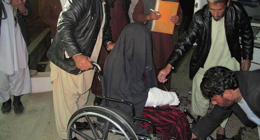 A wounded Afghan woman  is brought to the hospital in Helmand province early on January 1, 2015