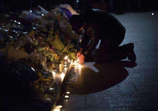 A man lights candles during a memorial ceremony for people who were killed in a stampede incident during a New Year's celebration on the Bund, in Shanghai January 1, 2015