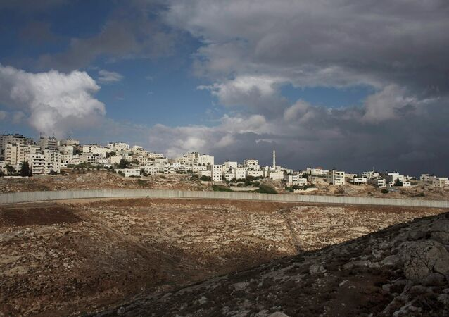 A section of the controversial Israeli barrier cuts beneath the West Bank refugee camp of Shuafat, October 31, 2014