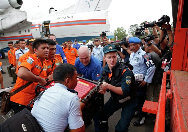 A Russian search and rescue team loads their equipment after arriving on a Beriev Be-200 amphibious plane to support the search for Indonesia AirAsia flight QZ8501