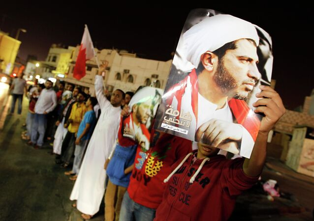 Protesters, holding placards with an image of Al Wefaq Secretary-General Sheikh Ali Salman, shout anti-government slogans as they gather outside Salman's home, in the village of Bilad Al Qadeem, south of Manama