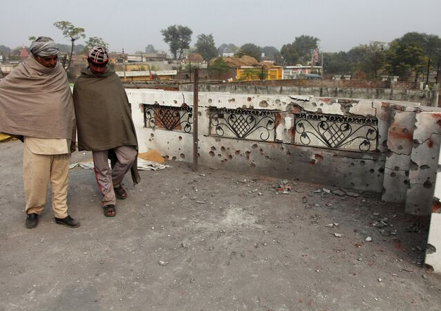Indian villagers inspect the damage on the roof of a house, caused allegedly by firing from the Pakistan side of the border