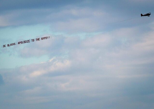 An airplane towing a banner reading de Blasio, apologize to the NYPD flies over the Hudson River in New York