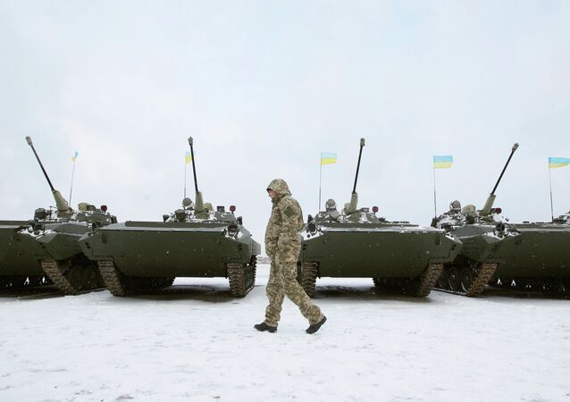 A Ukrainian serviceman walks past reconditioned armoured personnel carriers (APCs)