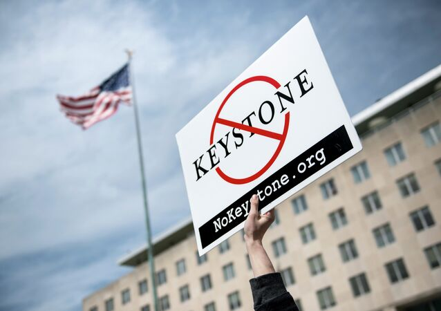 An activist holds up a sign outside the State Department during a protest of the Keystone XL pipeline on March 7, 2014 in Washington