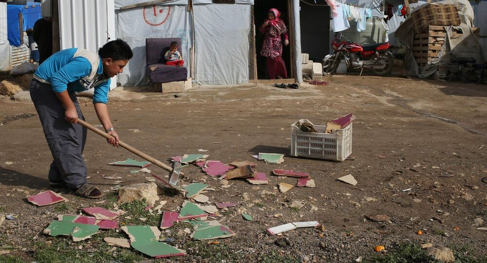 A Syrian boy chops scrap wood outside of his tent in preparation for the possibility of a snow storm at a refugee camp in Deir Zannoun village, Bekaa valley, Lebanon, Tuesday, Jan. 6, 2015