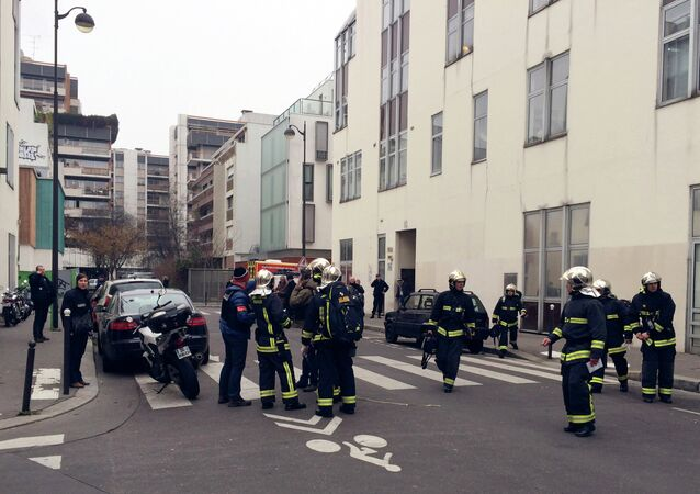 Police officers and firefighters gather in front of the offices of the French satirical newspaper Charlie Hebdo in Paris on January 7, 2015