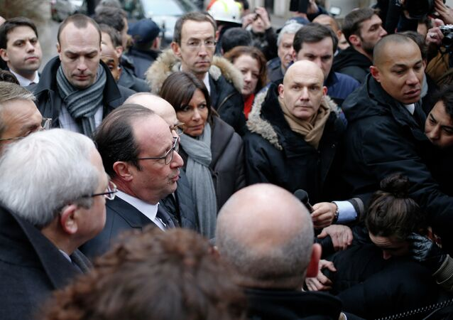 French President Francois Hollande (C) speaks to the press after arriving at the headquarters of the French satirical newspaper Charlie Hebdo in Paris on January 7.