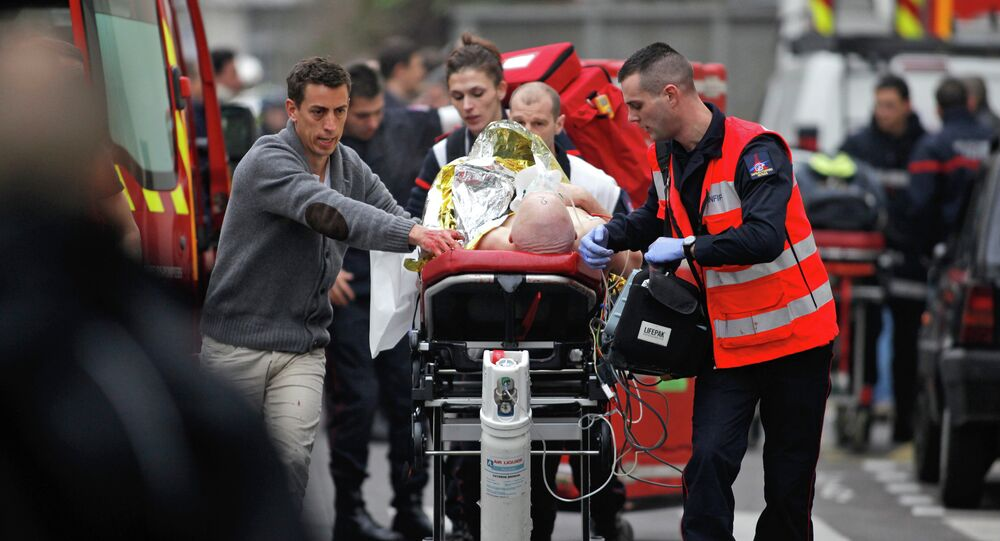 An injured person is transported to an ambulance after a shooting