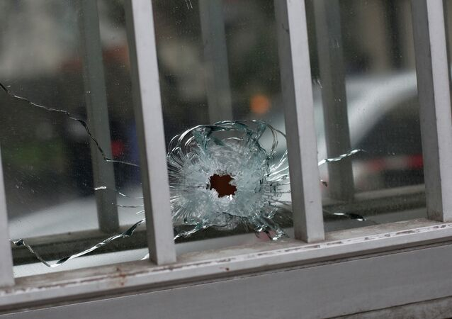 A bullet impact is seen in a window of a building next to the French satirical newspaper Charlie Hebdo's office, in Paris, Wednesday, Jan. 7, 2015. Masked gunmen shouting Allahu akbar! stormed the Paris offices of a satirical newspaper Wednesday, killing at least 12 people, including the paper's editor, before escaping in a getaway car.