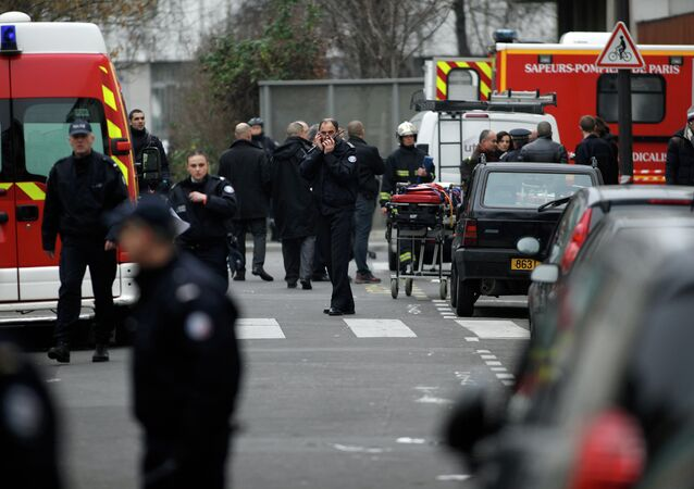 Police officers and firemen gather outside the French satirical newspaper Charlie Hebdo's office, in Paris, Wednesday, Jan. 7, 2015