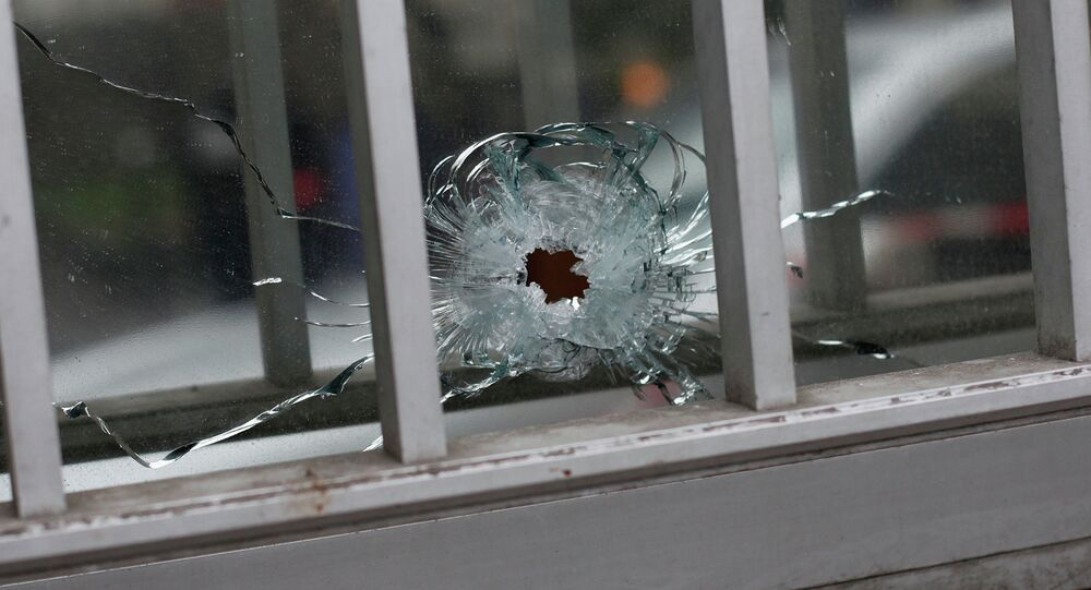 A bullet impact is seen in a window of a building next to the French satirical newspaper Charlie Hebdo's office, in Paris