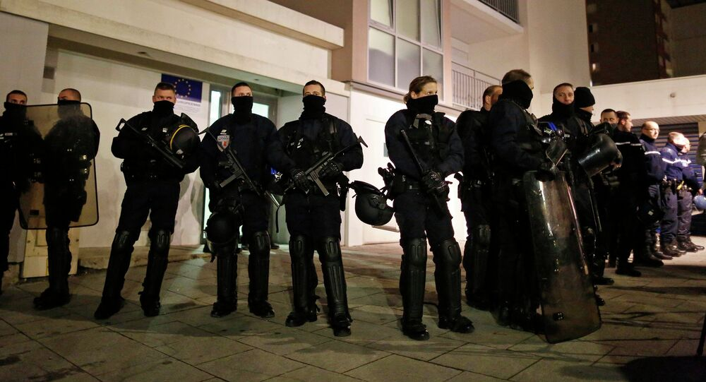 Police officers secure access to a residential building during investigations in the eastern French city of Reims January 8, 2015
