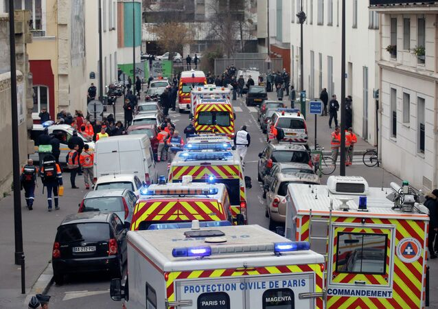 Ambulances gather in the street outside the French satirical newspaper Charlie Hebdo's office, in Paris, Wednesday, Jan. 7, 2015