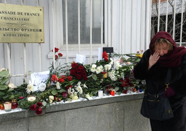 People bring flowers and candles to French embassy in Moscow, January 8, 2015.