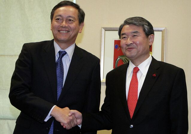 Japanese Vice Foreign Minister Akitaka Saiki, left, shakes hands with his South Korean counterpart Cho Tae-yong