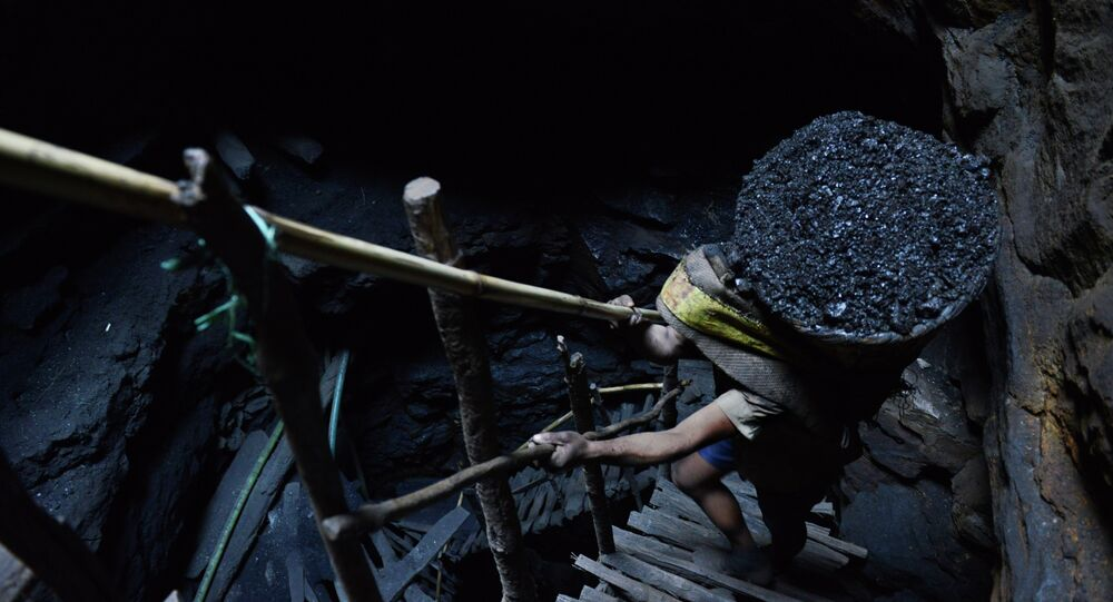 A miner slowly carries a heavy load of wet coal