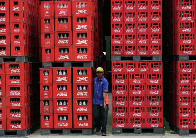 A worker walks through bottles at Coca Cola plant in Cibitung , West Java, Indonesia, Thursday, Feb. 24, 2011