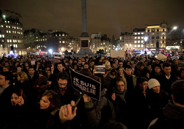 People hold up pens and posters reading 'I am Charlie' in French as they take part in a vigil of people, including many who were French, to show solidarity with those killed in an attack at the Paris offices of weekly newspaper Charlie Hebdo, in Trafalgar Square, London, Wednesday, Jan. 7, 2015