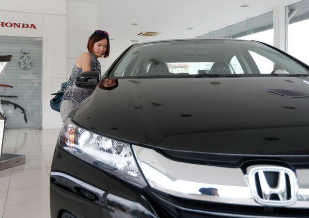 In this Dec. 22, 2014 photo, a woman checks out a new Honda City at a Honda showroom in Petaling Jaya, Malaysia