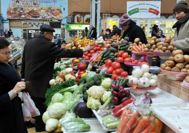 People look at vegetables in a market in Kiev