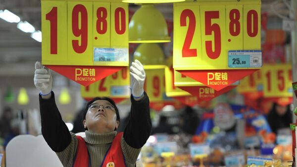 An employee adjusts a price tag at a supermarket in China - Sputnik International